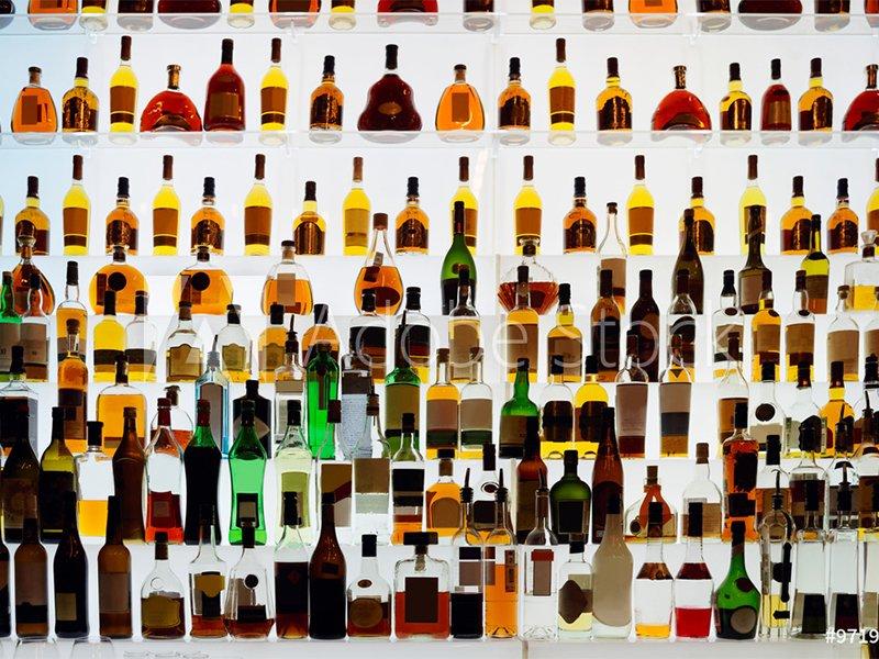 many liquor bottles on shelf lit from behindSideshowPete