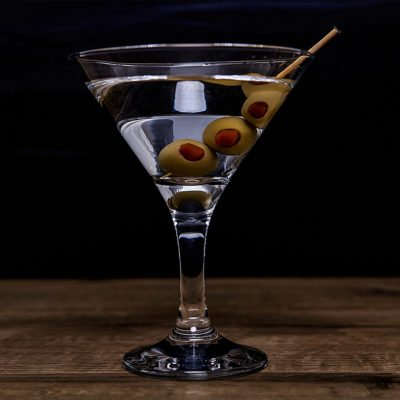 Dry Martini with three olives on wood