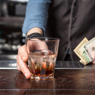 Man serving bar cocktail with money